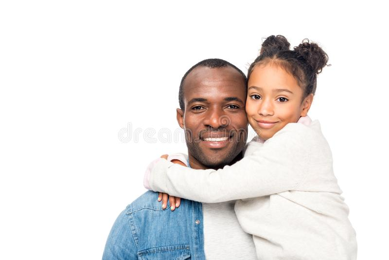 pai bonito e filha afro-americanos felizes que abraçam e que sorriem na câmera imagem de stock