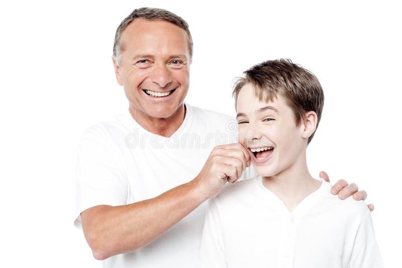 Pai brincalhão e filho, comprimindo mordentes imagem de stock royalty free