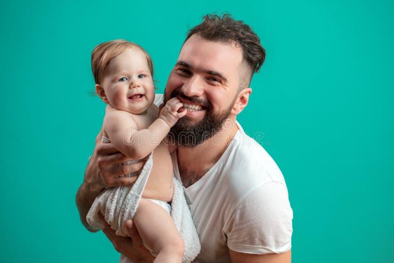 Pai brincalhão que leva sua criança infantil de sorriso no pescoço sobre o fundo azul foto de stock