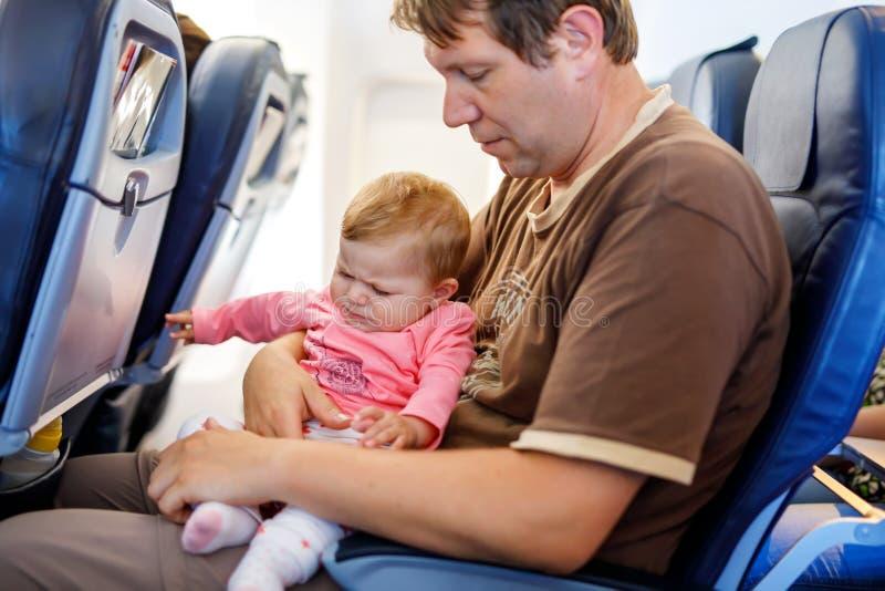 Pai cansado novo e sua filha de grito do beb? durante o voo no avi?o que vai em f?rias imagem de stock royalty free