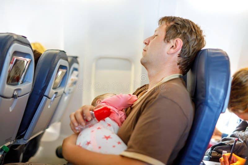 Pai cansado novo e sua filha do bebê que dormem durante o voo no avião que vai em férias imagens de stock royalty free