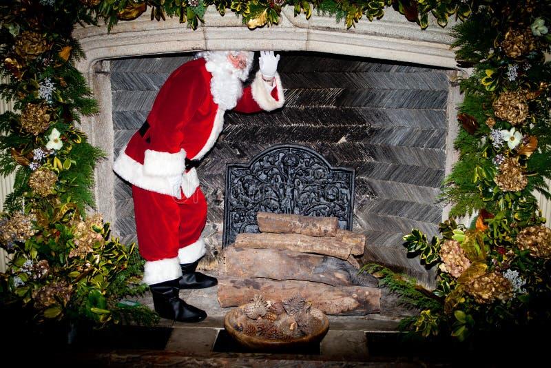 Pai Christmas que clumbing acima de uma chaminé imagens de stock royalty free