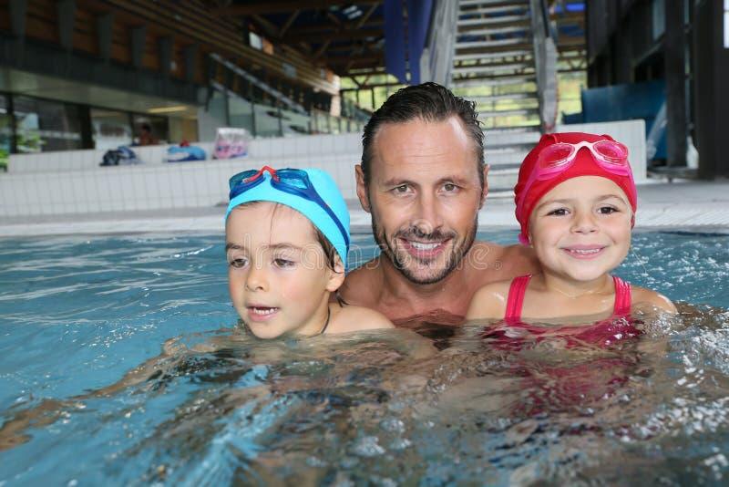 Pai com as crianças na piscina que tem o divertimento fotografia de stock