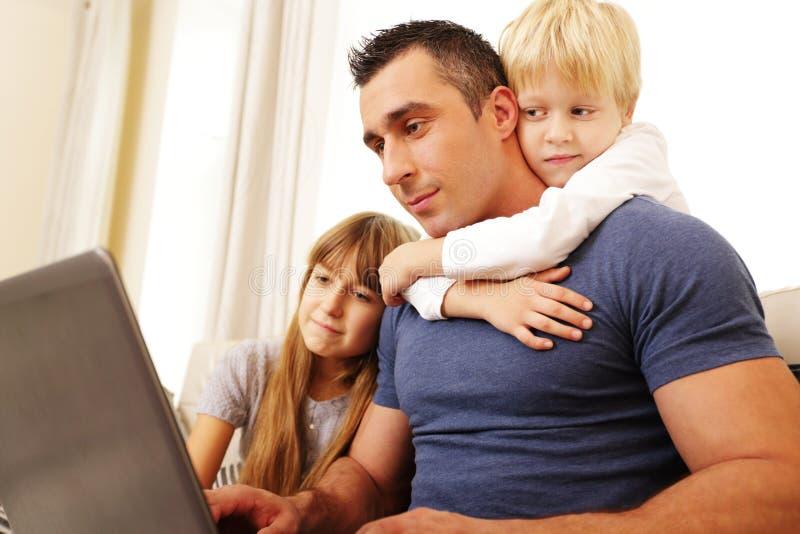 Pai com as crianças que trabalham no laptop imagem de stock
