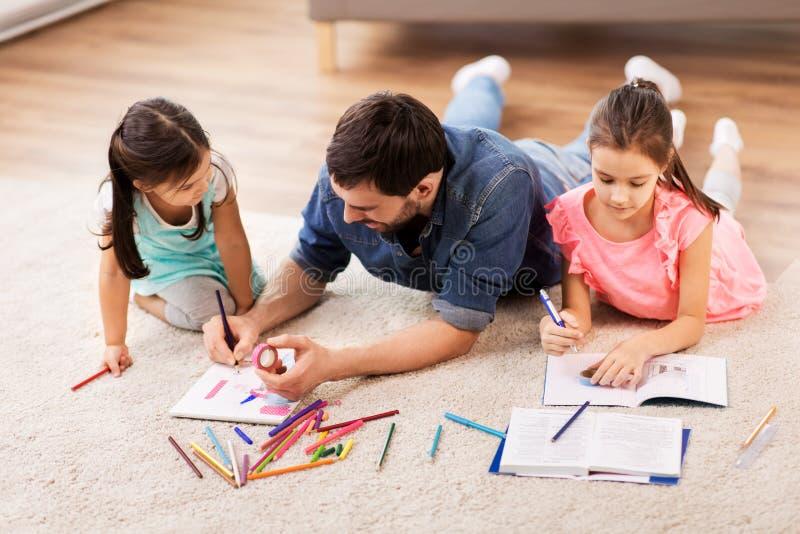 Pai com as filhas pequenas que tiram em casa imagem de stock royalty free