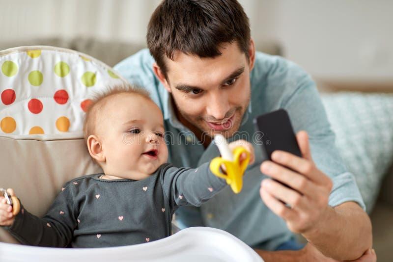 Pai com a filha do bebê que toma o selfie em casa fotos de stock royalty free