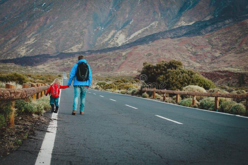 Pai com a filha pequena que anda na estrada nas montanhas fotografia de stock