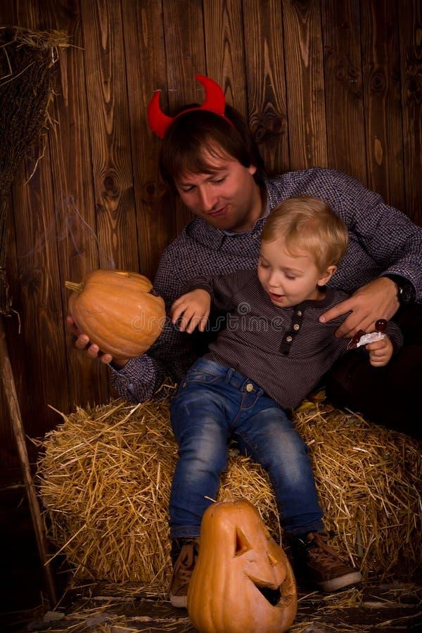 Pai com o filho do bebê no partido de Dia das Bruxas fotografia de stock royalty free