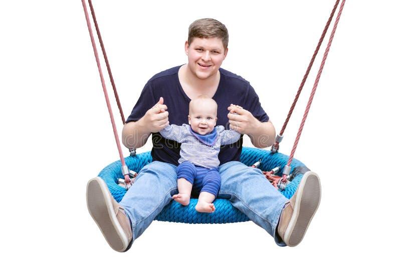 Pai com o filho que senta-se no balanço e no riso chain modernos grandes Parent com o bebê que aprecia o balanço na balancê no ca imagens de stock