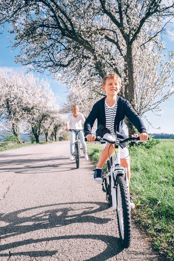 Pai com o passeio do filho bicicletas na estrada secundária sob o blosso foto de stock royalty free
