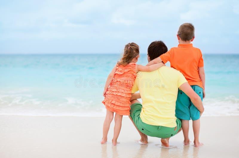 Pai com os miúdos na praia fotografia de stock