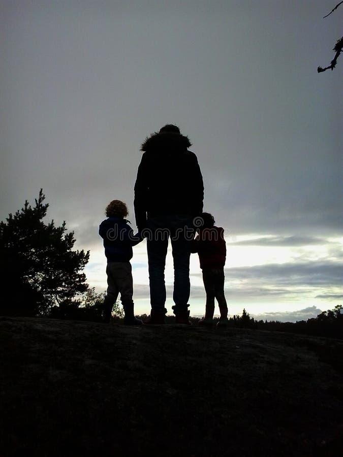 Pai com por do sol do relógio das crianças imagens de stock