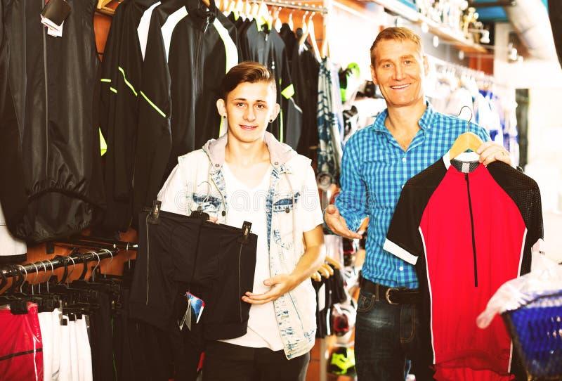 Pai com roupa de compra do filho para bicycling imagem de stock royalty free