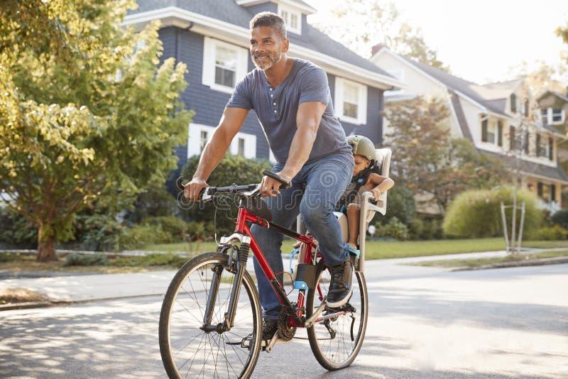 Pai Cycling Along Street com a filha na criança Seat imagens de stock