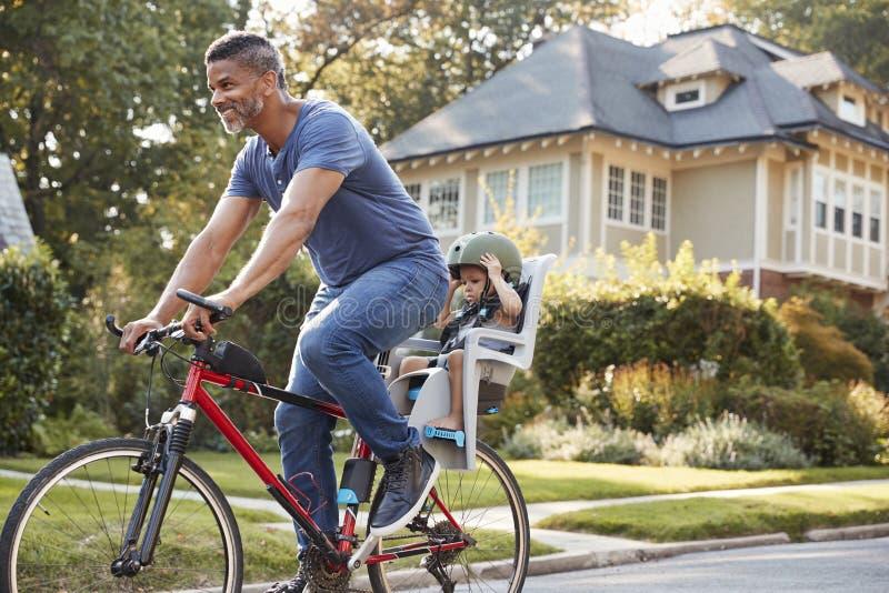 Pai Cycling Along Street com a filha na criança Seat imagem de stock