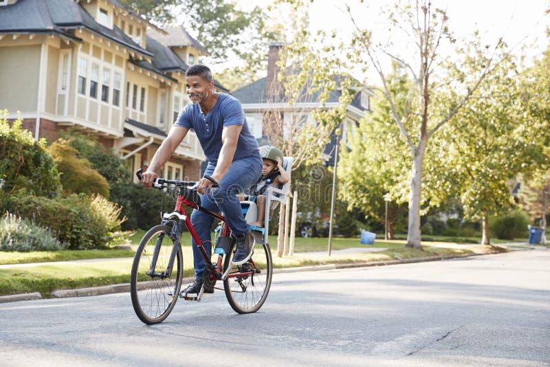 Pai Cycling Along Street com a filha na criança Seat fotografia de stock royalty free