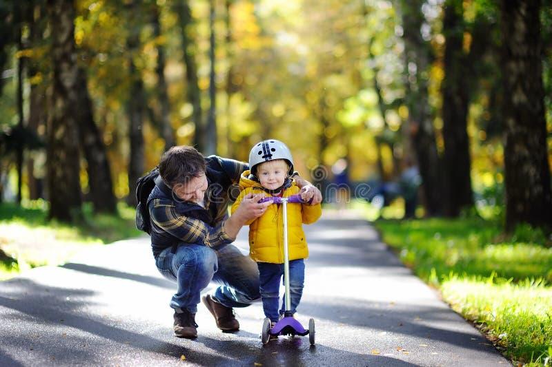 Pai da Idade Média que mostra a seu filho da criança como montar um 'trotinette' em um parque do outono fotografia de stock