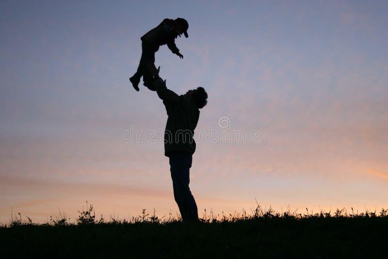 Pai da silhueta com criança fotografia de stock