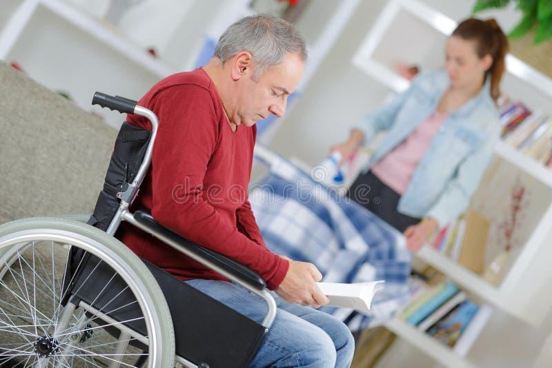 Pai de ajuda da filha na cadeira de rodas em casa imagem de stock