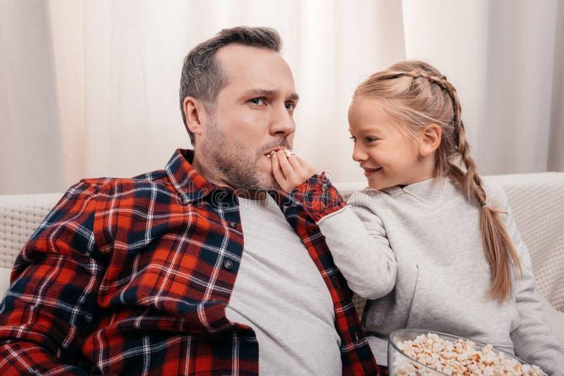 pai de alimentação de sorriso da menina com pipoca imagens de stock royalty free