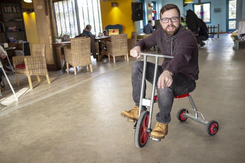 Pai de encantamento com uma barba e vidros, tomou uma bicicleta das crianças de seu filho, felizmente montando e dizendo algo, mo imagem de stock