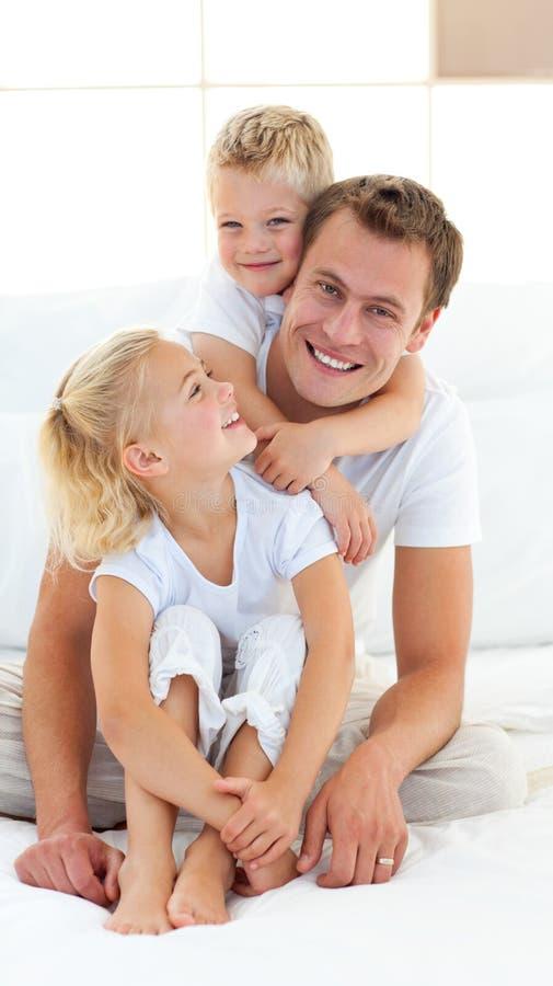 Pai de inquietação com suas crianças que sentam-se na cama fotografia de stock royalty free