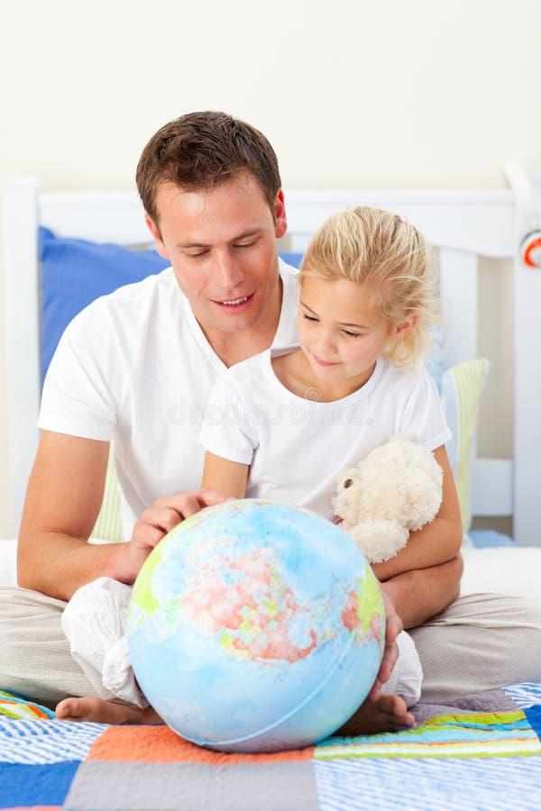 Pai de inquietação e sua filha que olham um globo foto de stock royalty free