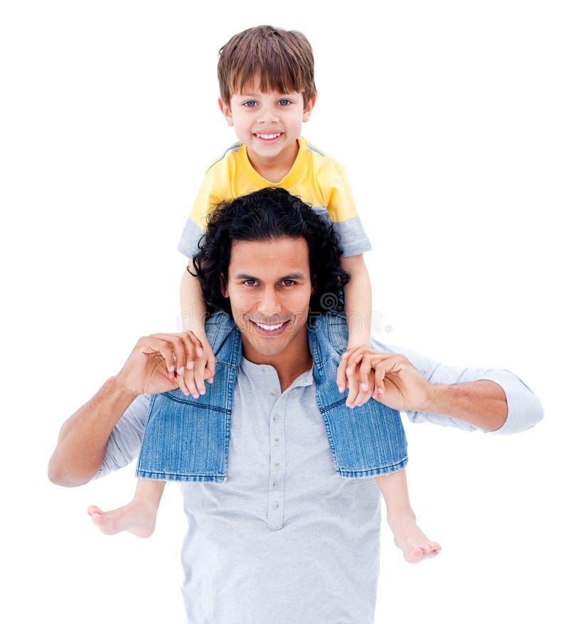 Pai de inquietação que dá às cavalitas o passeio a seu menino foto de stock