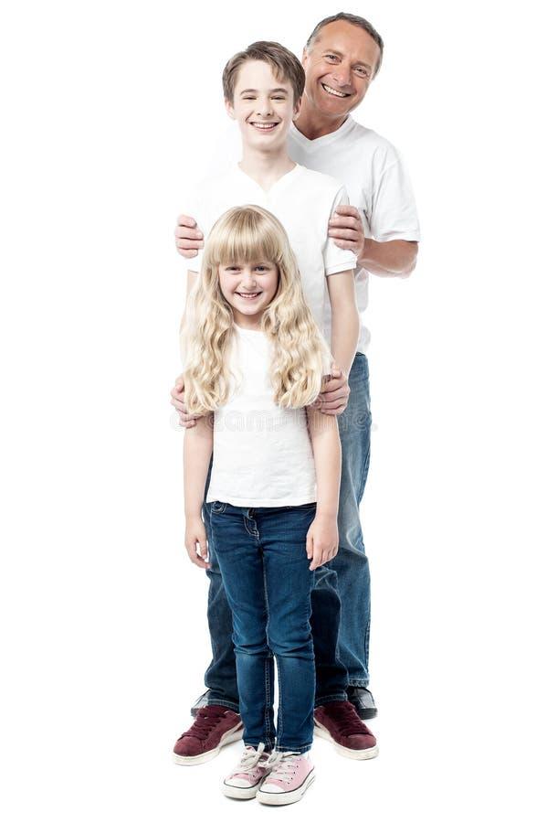 Pai de sorriso com as crianças que estão em seguido fotos de stock