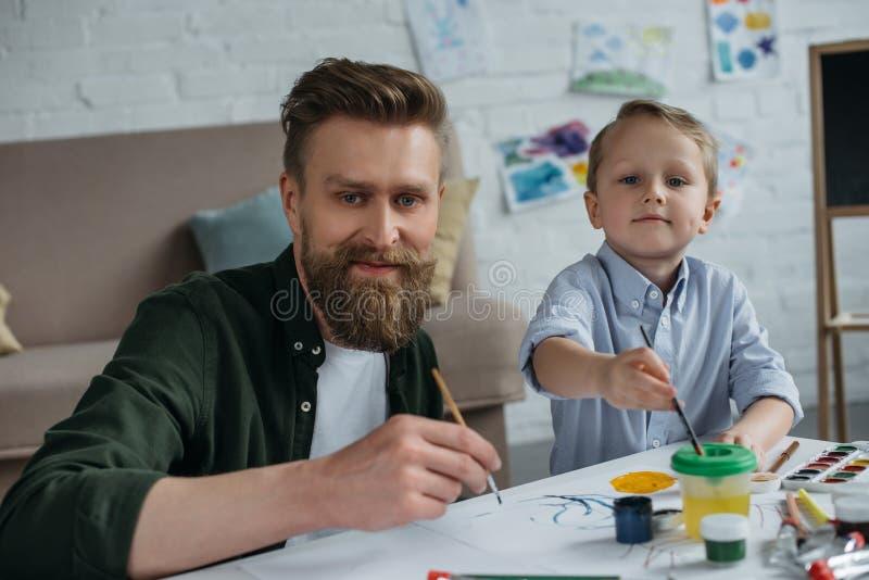 pai de sorriso e filho pequeno bonito com as pinturas e as escovas que olham a câmera junto imagem de stock royalty free