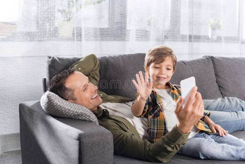 pai de sorriso e filho pequeno que usa o smartphone ao descansar no sofá imagens de stock royalty free