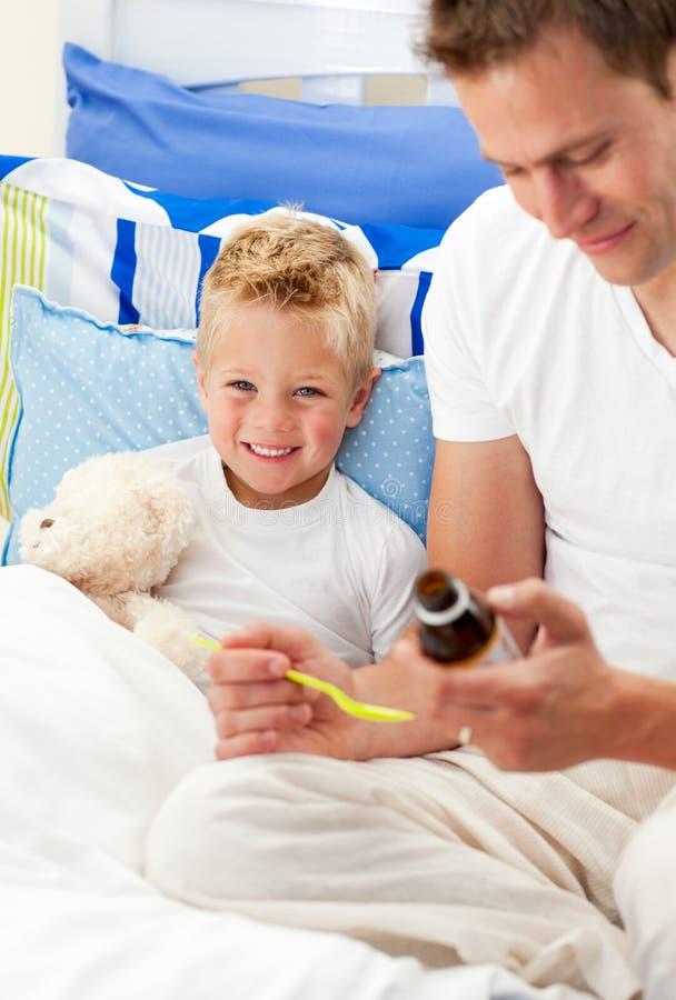 Pai de sorriso que dá o xarope da tosse a seu filho doente foto de stock royalty free
