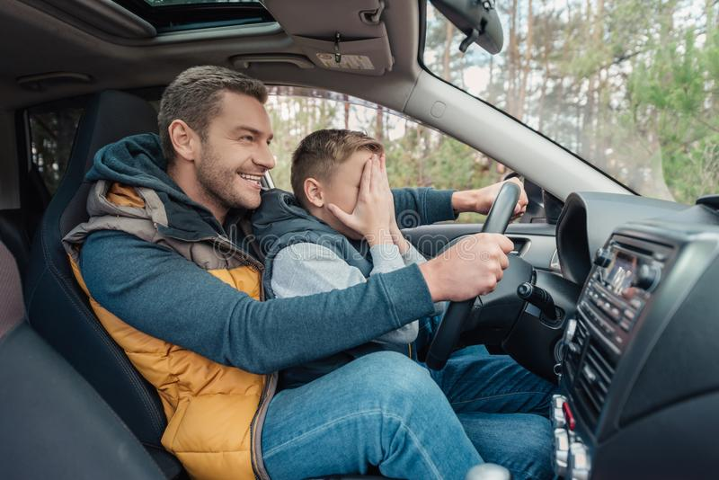 pai de sorriso que ensina o filho pequeno assustado que conduz o carro imagem de stock royalty free