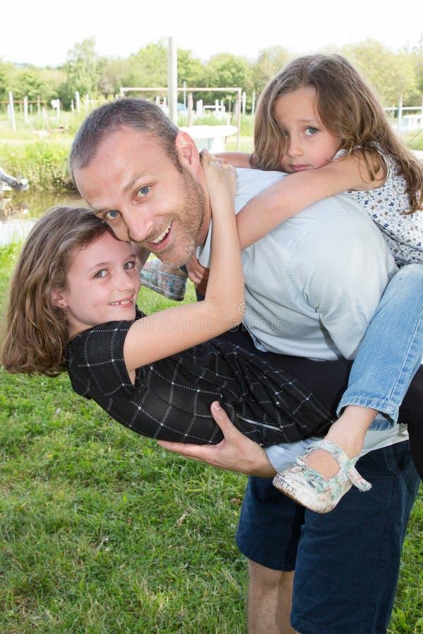 Pai do retrato e filha dois na felicidade na parte externa no dia de verão do prado imagens de stock