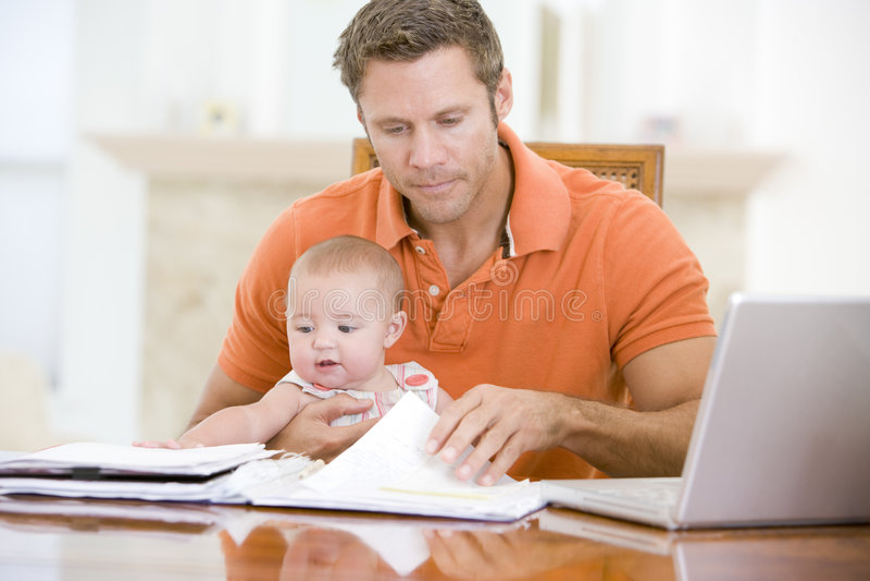 Pai e bebê na sala de jantar com portátil foto de stock royalty free