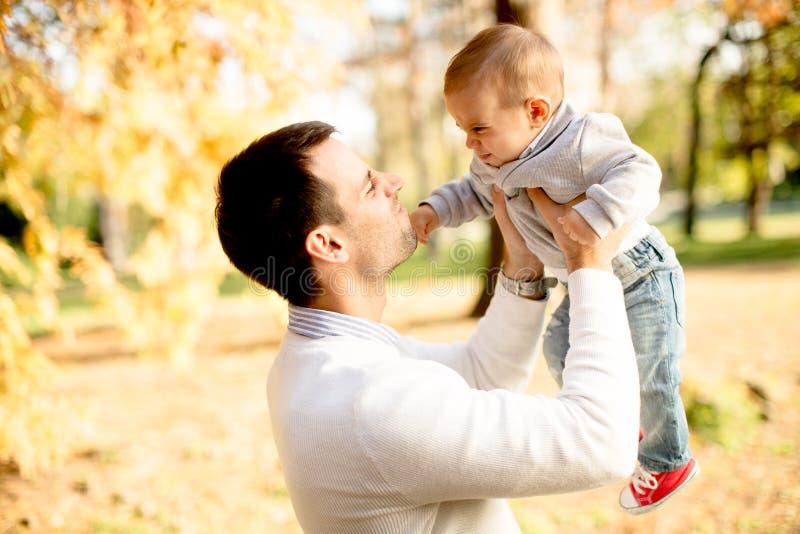 Pai e bebê novos no parque do outono foto de stock royalty free