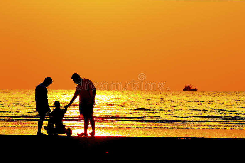 Pai e criança pela costa de mar, por do sol fotografia de stock royalty free