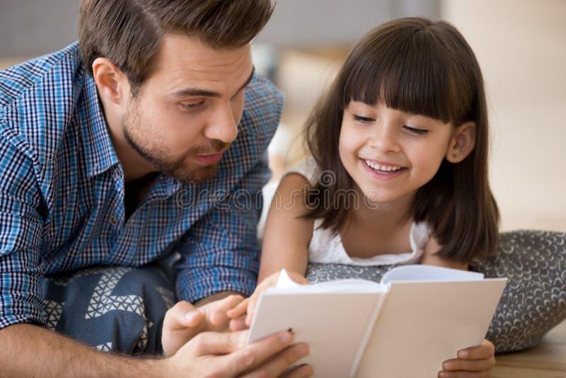 Pai e criança que encontram-se no assoalho morno que lê um livro imagem de stock royalty free