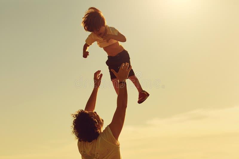 Pai e criança que jogam na natureza no por do sol imagem de stock