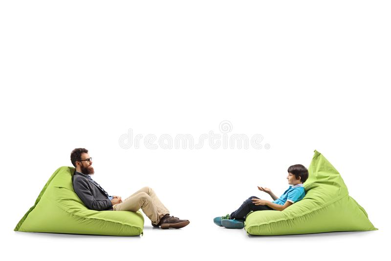 Pai e criança que sentam-se em sacos de feijão fotos de stock
