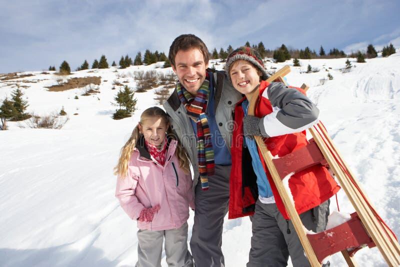 Pai e crianças novos na neve com trenó imagem de stock