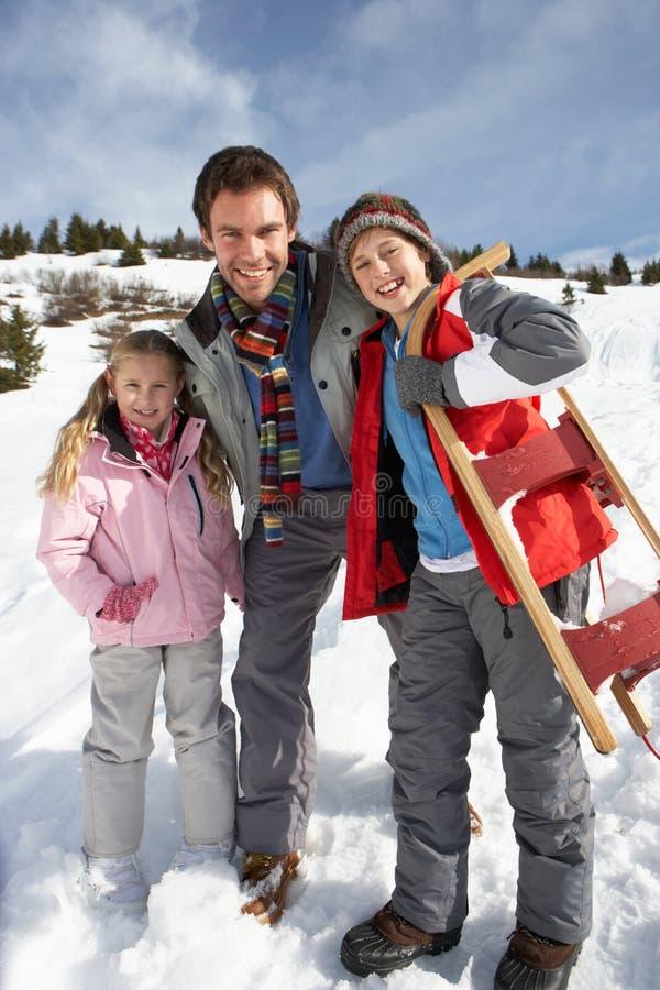 Pai e crianças novos na neve com trenó fotografia de stock royalty free