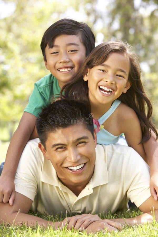 Pai e crianças que apreciam o dia no parque fotos de stock royalty free