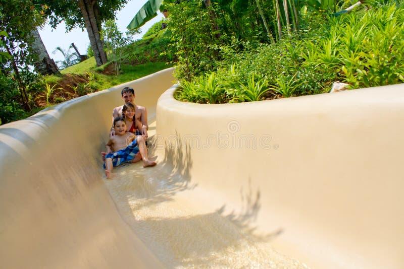 Pai e crianças que deslizam para baixo a corrediça de água foto de stock royalty free