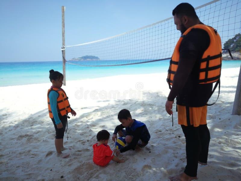 Pai e crianças que esperam uma viagem da lancha em uma ilha tropical foto de stock