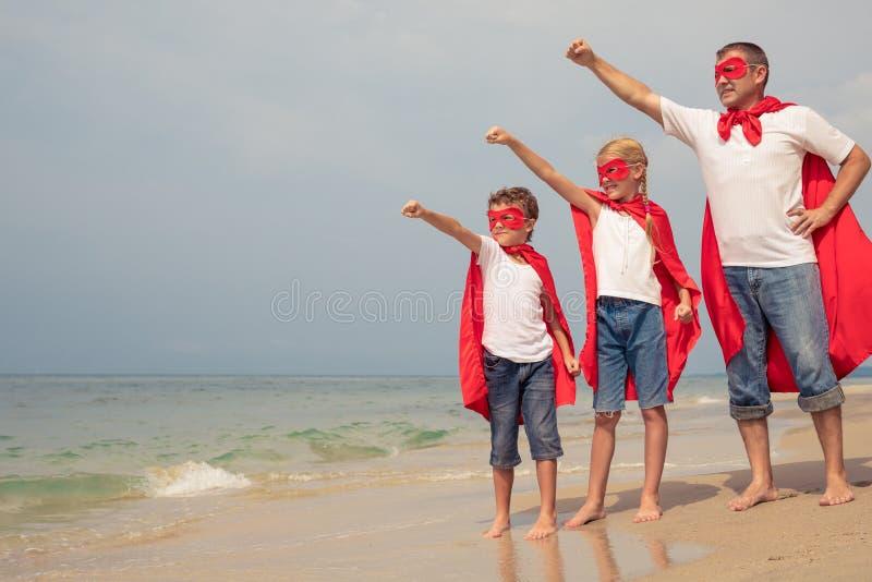 Pai e crianças que jogam o super-herói na praia no si do dia imagem de stock