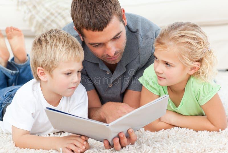 Pai e crianças que lêem um livro no assoalho