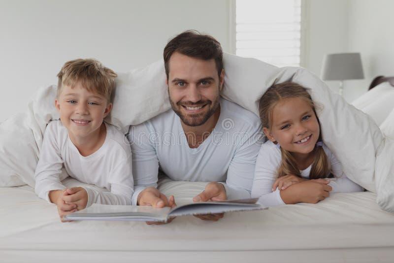 Pai e crianças que leem um livro sob a cobertura foto de stock