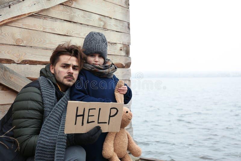 Pai e crian?a pobres com sinal da AJUDA no beira-rio fotos de stock