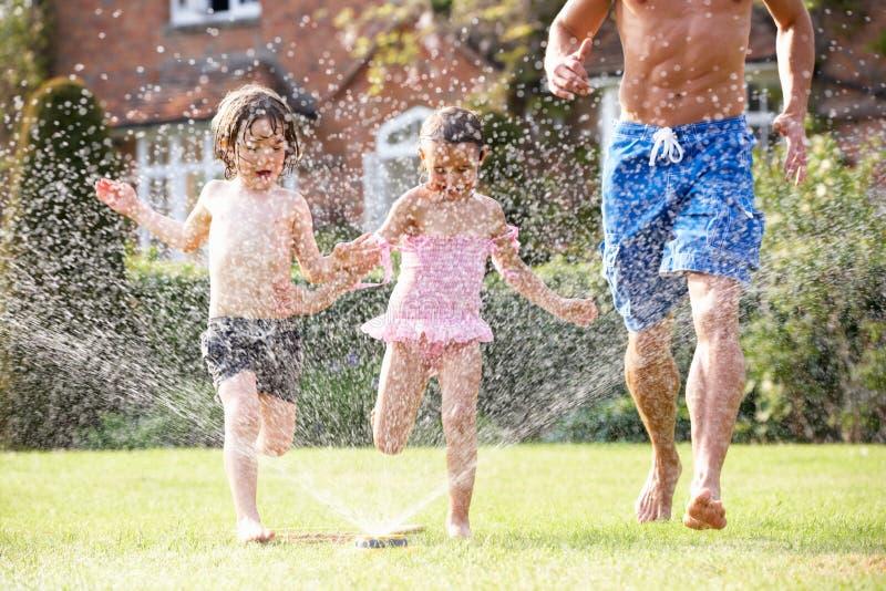 Pai e duas crianças que funcionam através do jardim imagem de stock royalty free